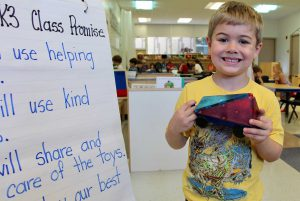 Photo of kindergarten student standing proudly in a classroom