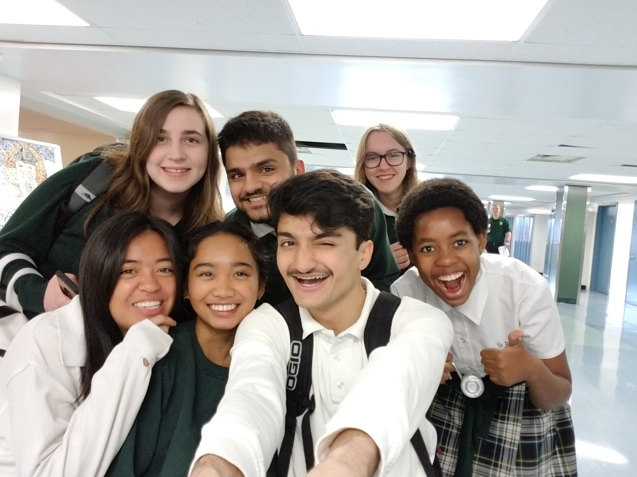 Photo of group of high school students in uniforms taking a selfie