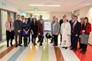 Photo of several OCSB delegates standing with plaque in school hallway