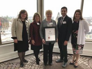 Photo of five OCSB staff members holding framed Top Employer plaque