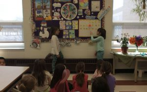 Photo of two students pointing to a Lenten calendar on the wall.