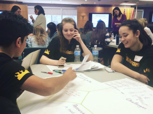 Photo os female students collaborating around desk