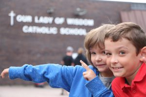 Photo of two elementary students pointing to their school