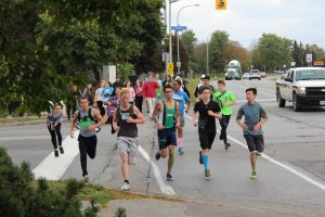 Photo of large group of high school students running in marathon