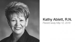 """Black and white photo of Trustee Kathy Ablett beside white background with black text that reads: """"Kathy Ablett, R.N. Passed away May 12, 2018"""""""