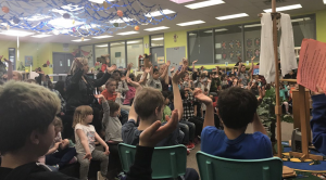 Photo of children raising their hands during school liturgy