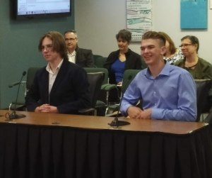 Photo of two students trustees sitting at presenter table in Boardroom