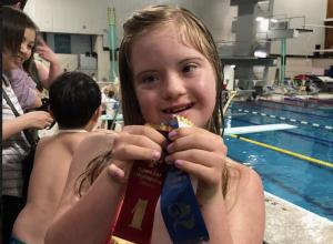 Photo of girl holding of winning ribbon at swim meet