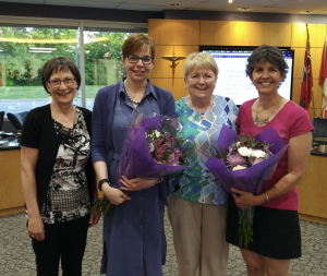Photo of Trustees and parent volunteers standing in Boardroom with flowers