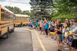 Photo of parents and teachers waving to kids on a school bus