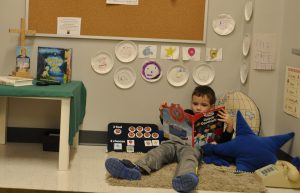 Photo of kindergarten student reading a book in a self-regulation space