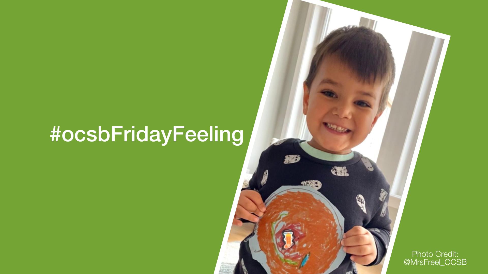 smiling boy holding artwork